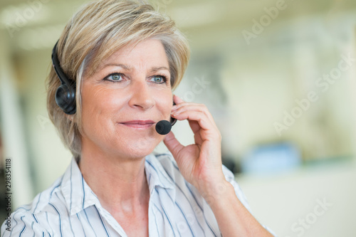 mature female customer-services worker wearing headset