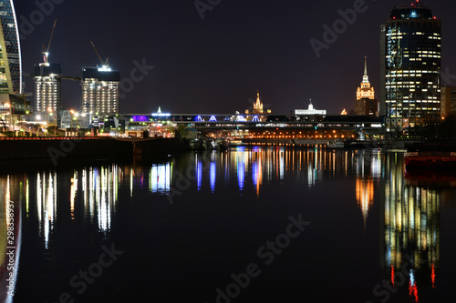 brightly lit tall buildings at night and reflected in the river Canvas Print