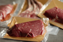 Raw Meat Vacuum-packed,  Steaks On A Wooden Board.