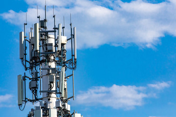 A closeup and detailed view of various GPS, cellphone, 3G, 4G and 5G equipped telecommunication tower as seen on cloudy blue sky with copy space