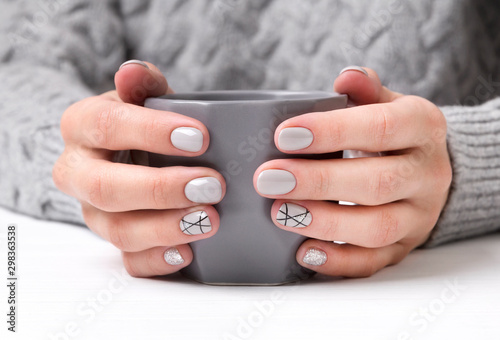 Woman's hands with geometric manicure nail design in cozy sweater