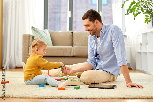 Fototapeta family, fatherhood and people concept - happy father and little baby daughter playing with wooden toy toy blocks kit at home obraz