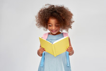 Childhood, School And Education Concept - Happy Little African American Girl With Backpack Reading Book Over Grey Background