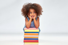 Childhood, School And Education Concept - Happy Smiling Little African American Girl With Pile Of Books Over Grey Background