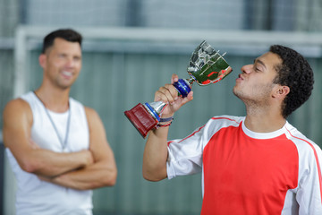 young man kissing his trophy