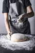 Posypywanie mąką chleba lub ciasta przez kucharza na ciemnym stole