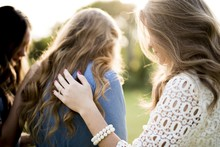 Closeup Shot Of A Female Blessing Her Friends With A Blurred Background