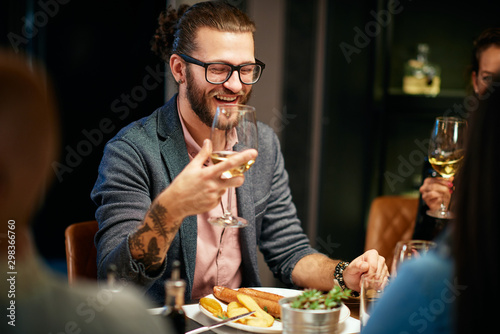 Handsome caucasian bearded hipster man with eyeglasses smiling and holding glass of wine while sitting with his friends in restaurant Fototapete
