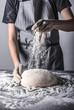 Posypywanie ciasta bochenka chleba mąką osoba w fartuchu piekarz