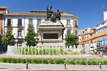 Monument To Isabel La Catolica And Cristobal Colon Against Bank Building , Of Granada. Monument Is Work Of Mariano Benlliure. Spain.