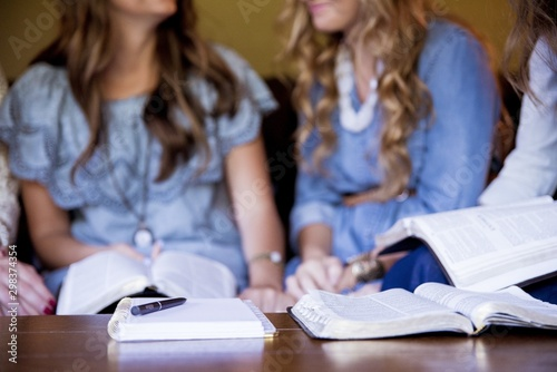 Valokuva Closeup shot of females sitting and reading the bible while taking notes with a