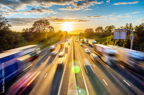 Fototapeta heavy traffic moving at speed on UK motorway in England at sunset obraz