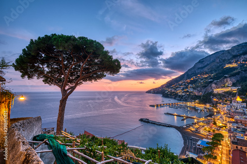 Photo View of Amalfi in Italy after sunset with a lone pine tree