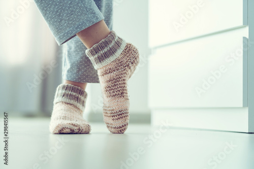 Obraz Woman in pajamas and cozy soft warm knitted winter socks at home - fototapety do salonu