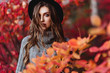 Fashion woman on a background of red and yellow autumn leaves