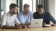 Diverse businessmen working together using apps looking at laptop screen