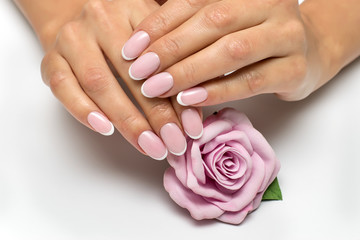 Classic manicure. Wedding nail design. White manicure. French Manicure on oval nails with a pink flower. Rose with nails.