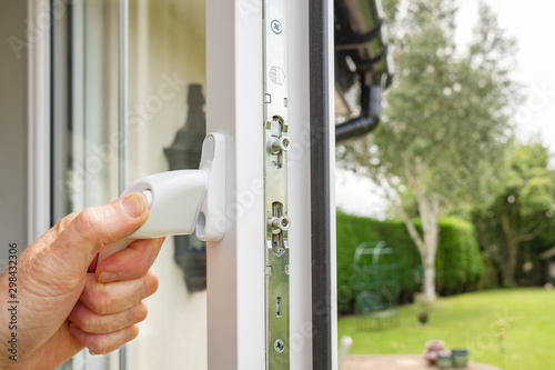 Person seen opening in a newly installed double glazed window on a house annex Canvas Print