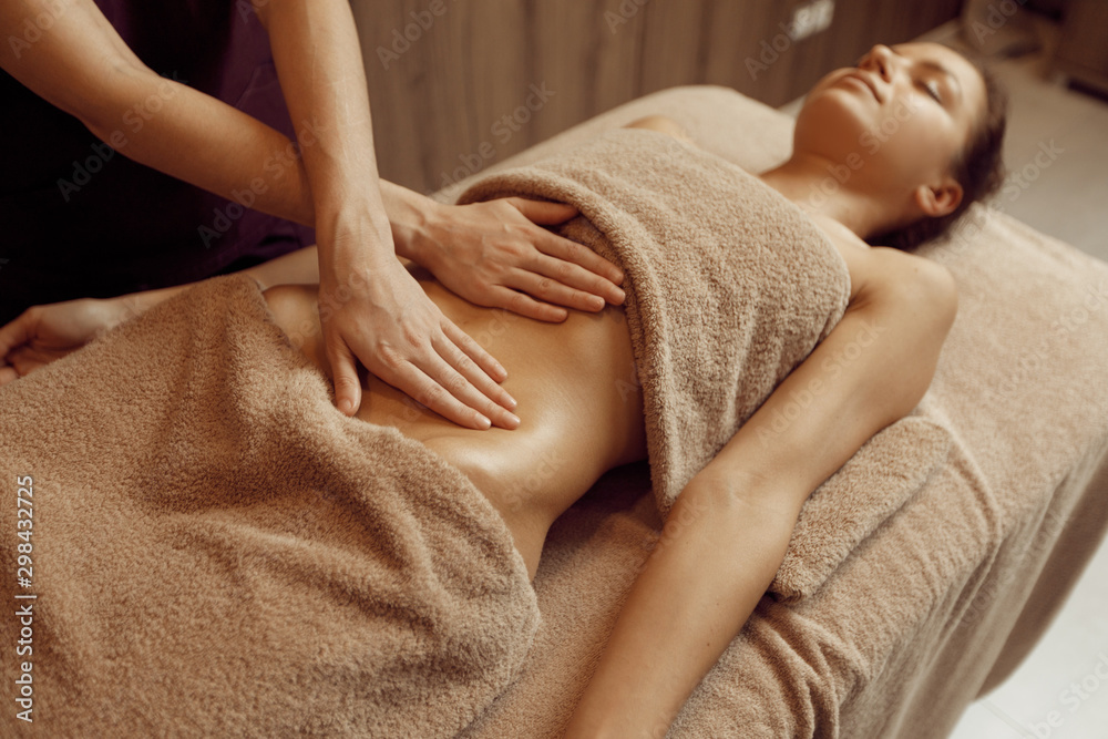 Fototapety, obrazy: Female masseur pampering stomach to young woman