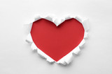 Torn heart shaped hole in white paper, top view. Red space for text