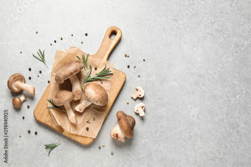 Flat lay composition with fresh wild mushrooms on light grey table, space for text