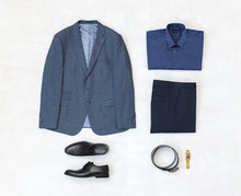 Suit Jacket, Pants, Blue Shirt, Black Shoes, Belt, Watch On Grey Background. Overhead View Of Classic Elegant Formal Men's Outfit. Set Of Stylish Men's Clothes And Accessories. Flat Lay, Top View.