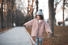 Smiling Kid Girl 3-4 Year Old Wearing Stylish Jacket And Hat Walking In Park Outdoors. Happy Child Posing Over Autumn Nature Background Closeup. Childhood.