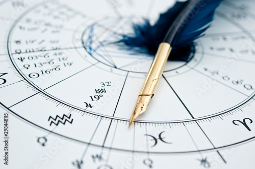 Photographie quill pen in form ob blue feather lying on horoscope and zodiac signs like astro
