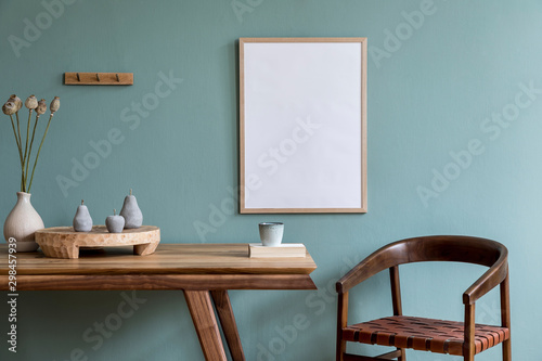 Fototapeta Stylish scandinavian dining room interior with mock up poster frame, wooden table, furniture, cup of coffee, flowers , cement fruits and elegant accessories. Ready to use. Template. Modern home decor. obraz