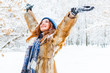 Leinwandbild Motiv charming young woman with raised hands rejoices in the winter forest