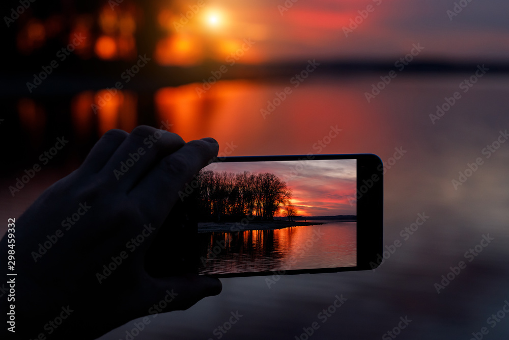 Fototapety, obrazy: Photographing sunset on a smartphone.
