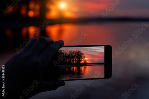 Foto auf Gartenposter Schwarz Photographing sunset on a smartphone.