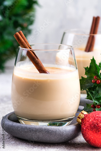 Foto auf Leinwand Alkohol New Year or Christmas Eggnog cocktail with cinnamon and nutmeg in a glass, branches of holly berries and ball toy on light stone background, festive decoration