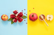 canvas print picture - Concept Rosh Hashanah postcard with copy space ; apples, pomegranates and honey on blue and yellow background