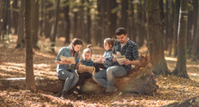 Family Together Reading Books In The Forest .