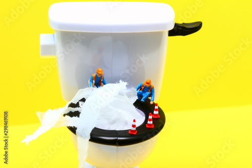 Fototapeta Conceptual image of a miniature figure workmen surveying a blocked toilet overflowing with tissue paper obraz