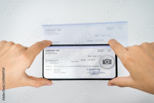 Fototapeta Woman Taking Photo Of Cheque To Make Remote Deposit obraz