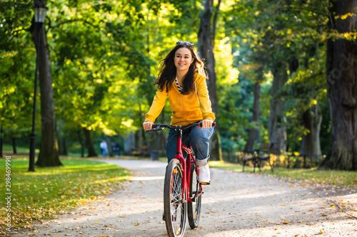 Fényképezés Urban biking - woman riding bike in city park