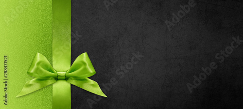 Photographie gift card wishes merry christmas background with green ribbon bow on black shiny