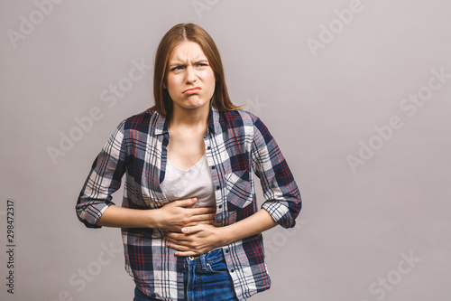 Photo Young beautiful woman having abdominal pain isolated on grey background