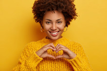 I Am Searching Key To Your Heart. Pretty Young Female Makes Love Gesture, Confesses And Expresses Truthful Feelings, Smiles Broadly, Shows White Even Teeth, Wears Yellow Sweater, Has Tender Look