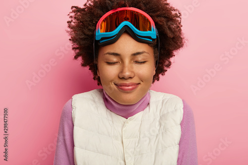 Fotografía  Close up portrait of happy female skier poses in white vest, snowboarding glasse