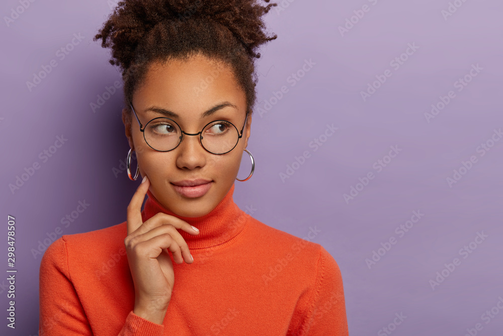 Fototapety, obrazy: Photo of thoughtful African American woman keeps index finger on cheek, looks aside with pensive expression, thinks what to do, wears round eyewear, silver earrings and poloneck, models indoor