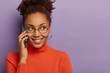 canvas print picture - Cheerful young dark skinned feminine girl has mobile phone conversation, wears round transparent glasses, has charming smile, hears good news, isolated over purple studio wall, copy space area