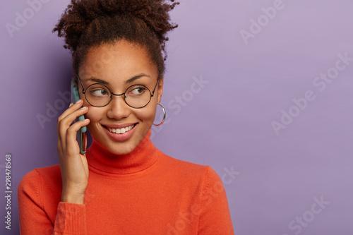 Fototapeta  Cheerful young dark skinned feminine girl has mobile phone conversation, wears r
