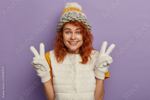 Valokuvatapetti Pleased ginger woman smiles pleasantly, raises hands and makes peace gesture, wears winter hat, mittens and white vest, being in good mood, isolated over purple background