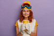 canvas print picture - Pleased female skier has coffee break after active riding, wears white mittens, t shirt, yellow hat and protective snowboarding glasses, smiles with dimples, isolated over purple background.
