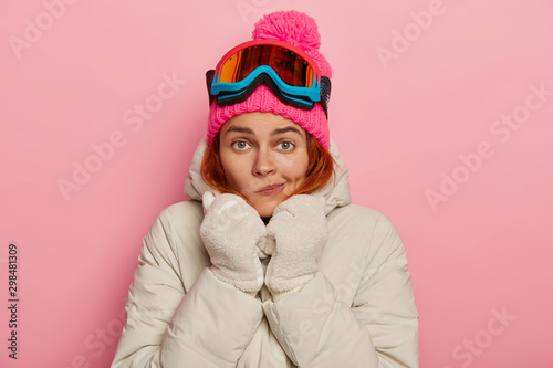 Photo of lovely European female traveler purses lips, warms herself in comfortab Fototapet
