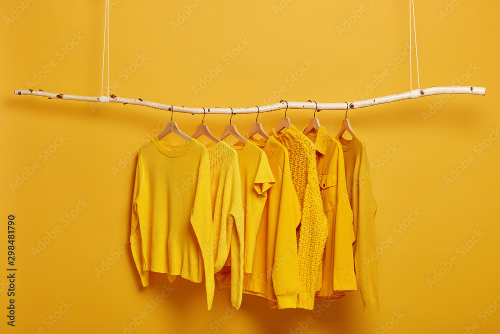 Fototapeta Collection of plain yellow sweaters and jackets for women hanging on rack in dressing room. Selective focus. Fashionable winter or autumn clothes. Sale in fashion store. Dressing closet with clothing