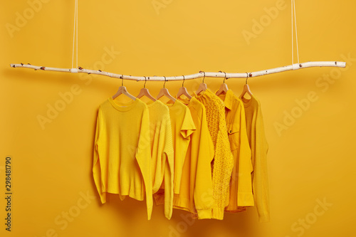 Obraz Collection of plain yellow sweaters and jackets for women hanging on rack in dressing room. Selective focus. Fashionable winter or autumn clothes. Sale in fashion store. Dressing closet with clothing - fototapety do salonu